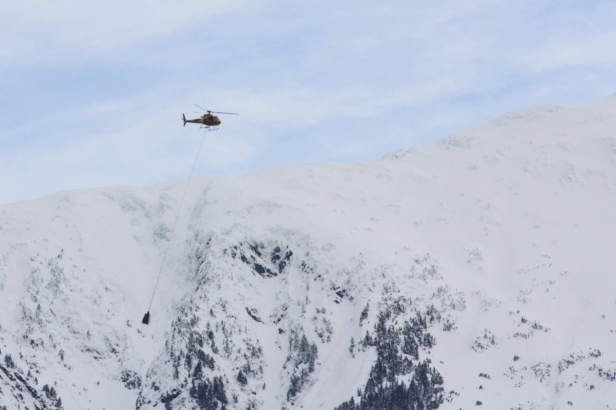 The Alaska Department of Transportation and Public Facilities, contracting with Coastal Helicopters, works to reduce avalanche risk on Thane Road by setting off avalanches in a controlled fashion on Feb. 5, 2021. City officials are currently considering adopting new maps that designate additional avalanche and landslide areas downtown. (Michael S. Lockett / Juneau Empire File)