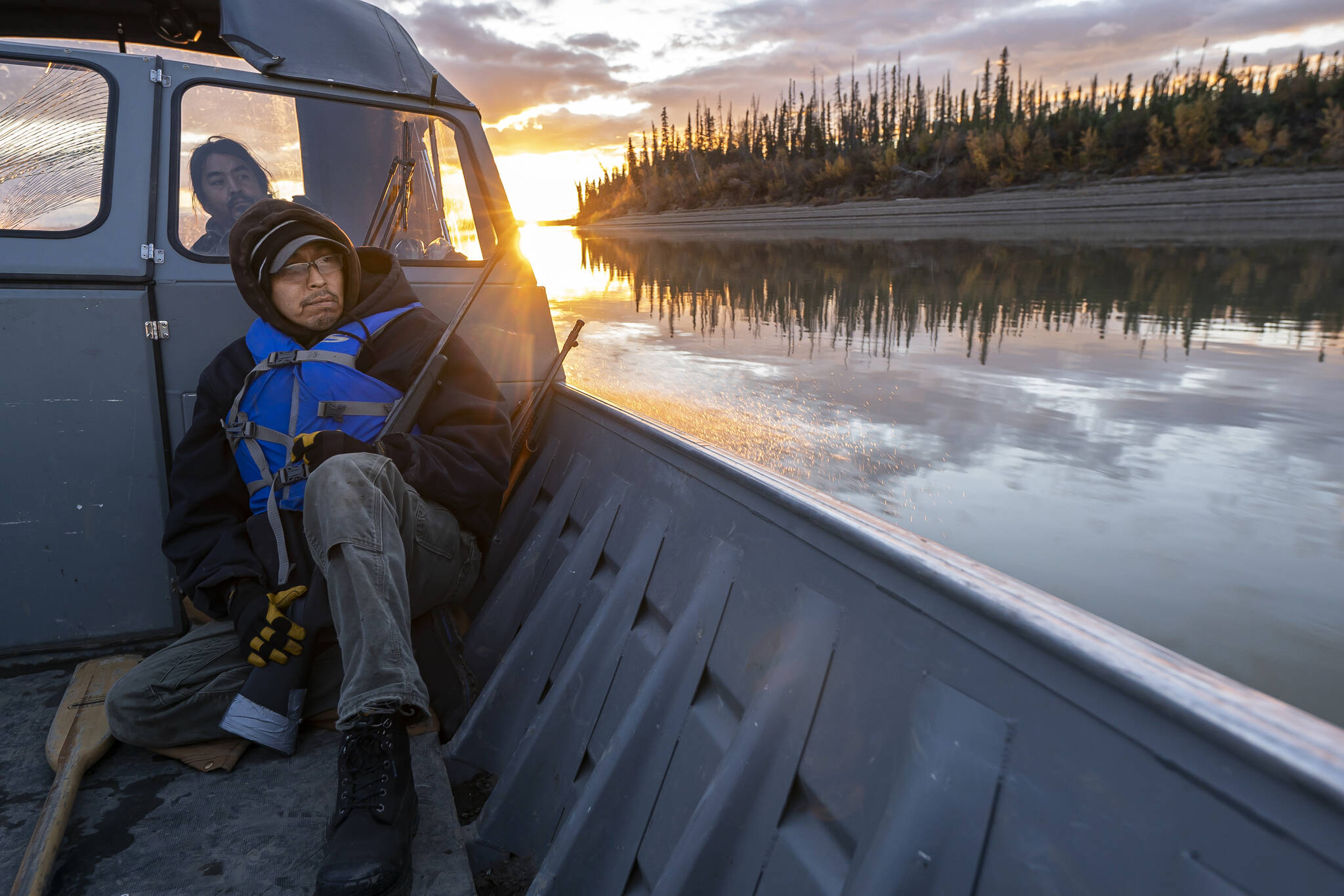 Michael Williams scans the shoreline for moose while traveling up the Yukon River on Tuesday, Sept. 14, 2021, near Stevens Village, Alaska. For the first time in memory, both king and chum salmon have dwindled to almost nothing and the state has banned salmon fishing on the Yukon. The remote communities that dot the river and live off its bounty are desperate and doubling down on moose and caribou hunts in the waning days of fall. (AP Photo/Nathan Howard)